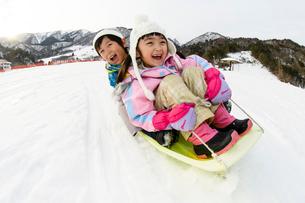 雪山でソリで遊ぶ子供の写真素材 [FYI03121481]