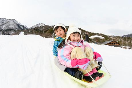 雪山でソリで遊ぶ子供の写真素材 [FYI03121483]