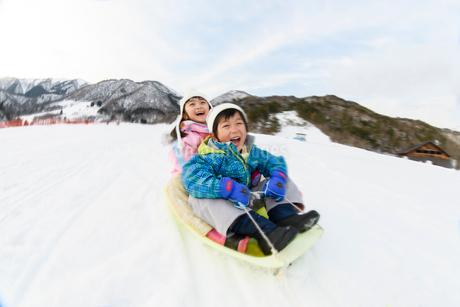 雪山でソリで遊ぶ子供の写真素材 [FYI03121486]
