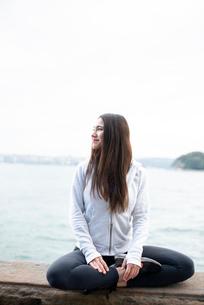 あぐらをかいて微笑んでいる女性の写真素材 [FYI03123578]