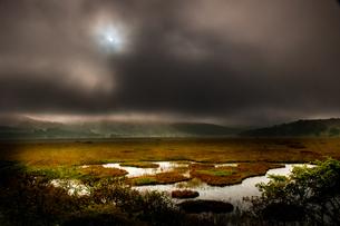 暗雲より太陽射しこむ霧ヶ峰高原草紅葉の八島ヶ原湿原の写真素材 [FYI03124261]