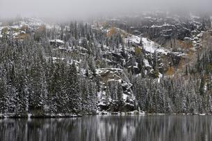 山岳湖と背景の岩肌を見せた針葉樹林に覆われた山肌に霧が迫りおりているの写真素材 [FYI03124305]