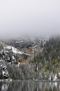 山肌を這い下りる霧と降雪後の針葉樹林を背景に広がる山岳湖の写真素材 [FYI03124307]