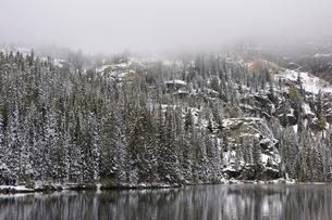 霧が山から迫る残雪に映える森と山岳湖の写真素材 [FYI03124317]