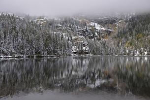 霧、雪、針葉樹とわずかに残る黄葉を背景に広がる山岳湖の写真素材 [FYI03124320]