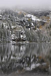 霧が山岳部に立ち込め残雪の中に黄葉したアスペンが見える山岳湖の写真素材 [FYI03124324]