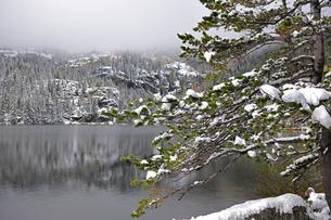 背景の山に霧がかかり雪が景観に味わいを与えている山岳湖の写真素材 [FYI03124356]