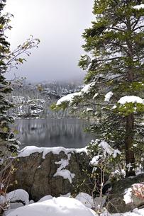背景の山を霧が覆いかぶさっていり残雪に映える山岳湖の写真素材 [FYI03124372]