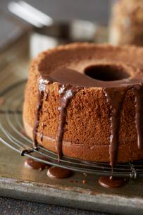 チョコソースをかけるチョコレートシフォンケーキの写真素材 [FYI03124592]