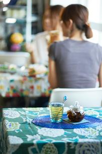青いテーブルクロスの テーブル越しに見える食事風景の写真素材 [FYI03124618]