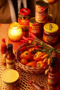 卓上のキャンドル、かごに入った野菜とピクルスなどの瓶詰、缶詰の写真素材 [FYI03124629]