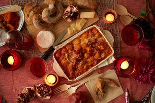 パーティのための 卓上のワイン、チーズとパン、グラタンの写真素材 [FYI03124631]