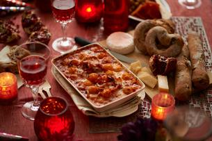 パーティのための 卓上のワイン、チーズとパン、グラタンの写真素材 [FYI03124632]