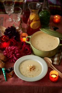 卓上でキャンドルに照らされた クルトンののったコーンスープの写真素材 [FYI03124634]