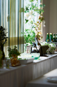 窓際のテーブルにセッティングされた シャンパンと花の写真素材 [FYI03124650]