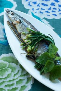 青いテーブルクロスの卓上の 白いお皿に盛られたさんまの写真素材 [FYI03124659]