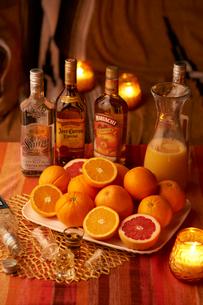 卓上でキャンドルに囲まれた 柑橘系フルーツと洋酒の写真素材 [FYI03124671]