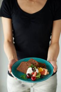 皿に盛ったチョコパウンドケーキを持つ女性の写真素材 [FYI03124877]