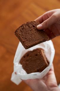 ワックスペーパーに包んだチョコのパウンドケーキを持つ女性の写真素材 [FYI03124883]