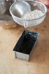 パウンドケーキ型に小麦粉を振る手の写真素材 [FYI03124896]