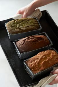 焼き上がったチョコと抹茶とナッツのパウンドケーキを持つ女性の写真素材 [FYI03124898]