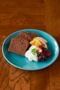皿に盛られたチョコパウンドケーキ、フルーツ添えの写真素材 [FYI03124901]