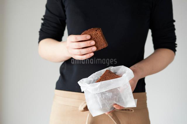 ワックスペーパーに包んだチョコのパウンドケーキを持つ女性の写真素材 [FYI03125266]
