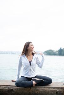 水辺であぐらをかいて笑っている女性の写真素材 [FYI03125595]