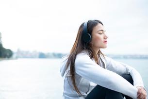水辺で目をつぶって音楽を聴いている女性の写真素材 [FYI03125773]