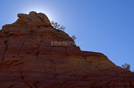 逆光に見上げる地層を見せる大きな赤岩の写真素材 [FYI03126973]