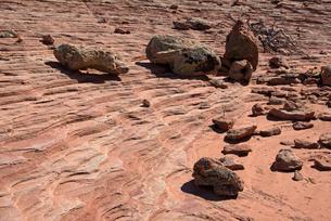 堆積岩が侵食によって削り出された傾斜部に転がる岩の写真素材 [FYI03126991]