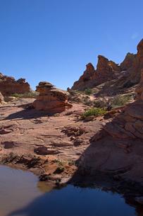 オアシスのように見える荒野の赤岩の手前に見える水溜りの写真素材 [FYI03127040]