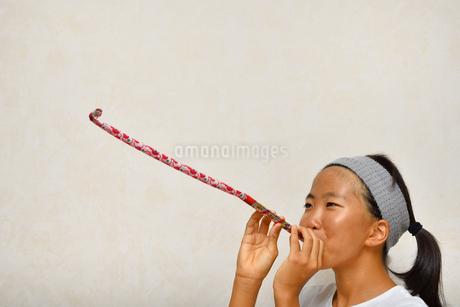 吹き戻しで遊ぶ女の子の写真素材 [FYI03127064]
