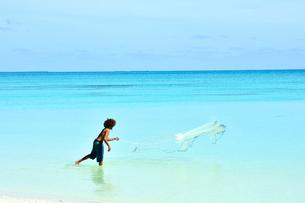 ニューカレドニア ウヴェア島のファヤウエ・ビーチで網で漁をする人の写真素材 [FYI03127255]