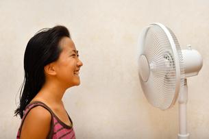 扇風機で涼む女の子の写真素材 [FYI03127435]