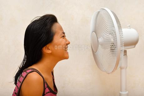 扇風機で涼む女の子の写真素材 [FYI03127436]