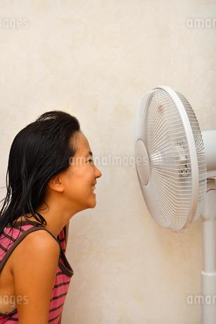 扇風機で涼む女の子の写真素材 [FYI03127437]