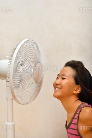 扇風機で涼む女の子の写真素材 [FYI03127440]