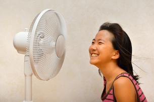扇風機で涼む女の子の写真素材 [FYI03127441]