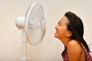 扇風機で涼む女の子の写真素材 [FYI03127442]