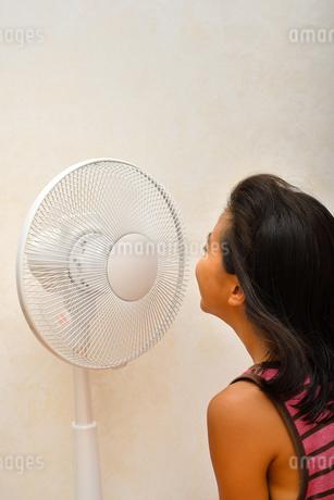 扇風機で涼む女の子(後姿)の写真素材 [FYI03127445]