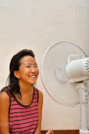 扇風機で涼む女の子の写真素材 [FYI03127446]