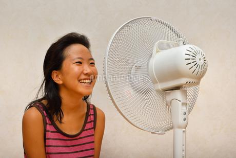 扇風機で涼む女の子の写真素材 [FYI03127447]
