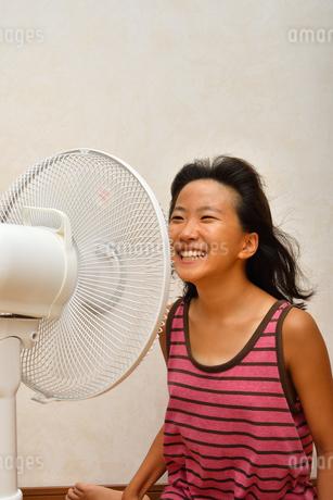 扇風機で涼む女の子の写真素材 [FYI03127449]