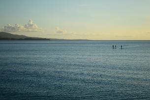 夕暮れの海のスタンドアップパドルボードの三人の写真素材 [FYI03127580]