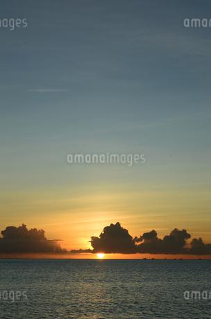 オレンジ色の夕日が水平線に落ちる穏やかな海の写真素材 [FYI03127644]