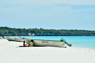 ニューカレドニア ウヴェア島の青い海とボートと二人の子供の写真素材 [FYI03127868]