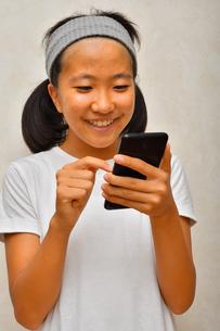 スマートフォンを操作する女の子の写真素材 [FYI03128383]