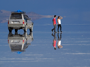 ウユニ塩湖の鏡張りの湖面を歩く観光客の写真素材 [FYI03131271]