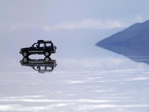 ウユニ塩湖に停められた車が鏡張りで宙に浮いているように見えるの写真素材 [FYI03131274]